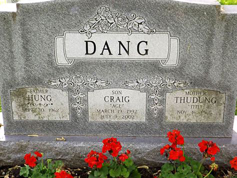 "A headstone reads ""Dang"" above the names of a mother, father, and son"