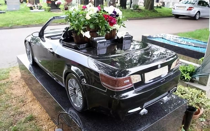A BMW Headstone is full of flowers