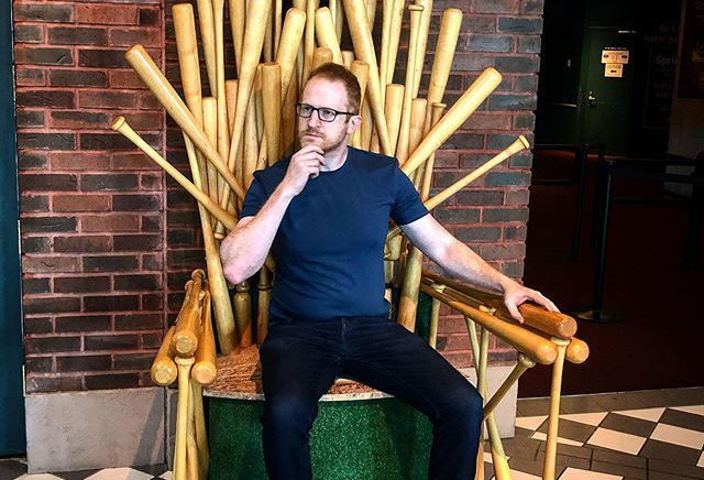 Comedian Steve Hofstetter sits on a baseball bat chair at the Negro Leagues Baseball Museum