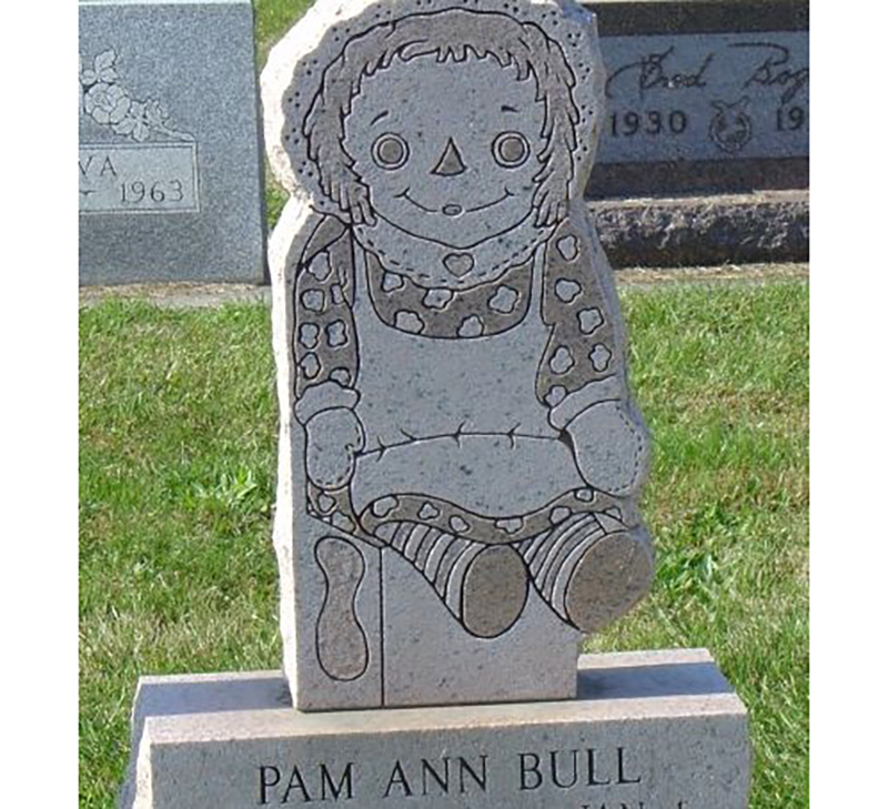 A headstone is made to look like a 2D Raggedy Ann