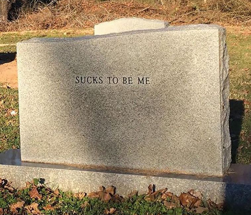 "A headstone reads ""sucks to be me"""