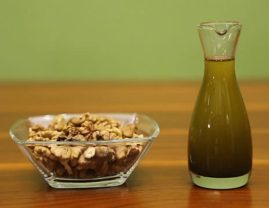 Homemade walnut oil sitting next to a bowl of walnuts