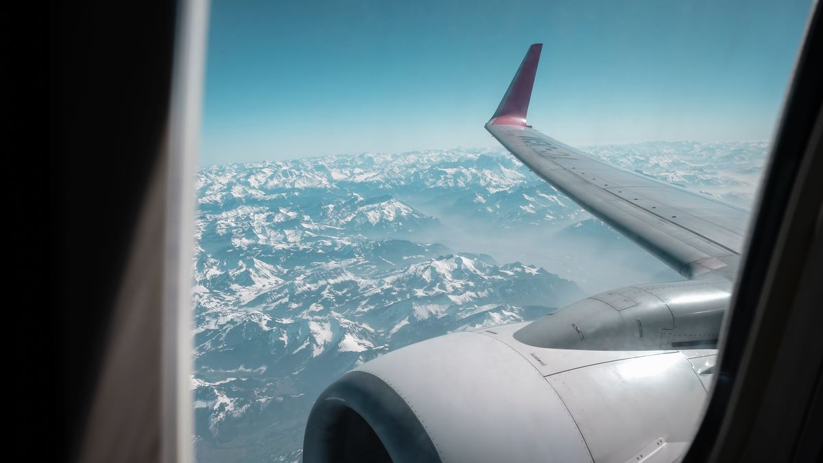 Looking out a window, an airplane flies over the Alps in Switzerland