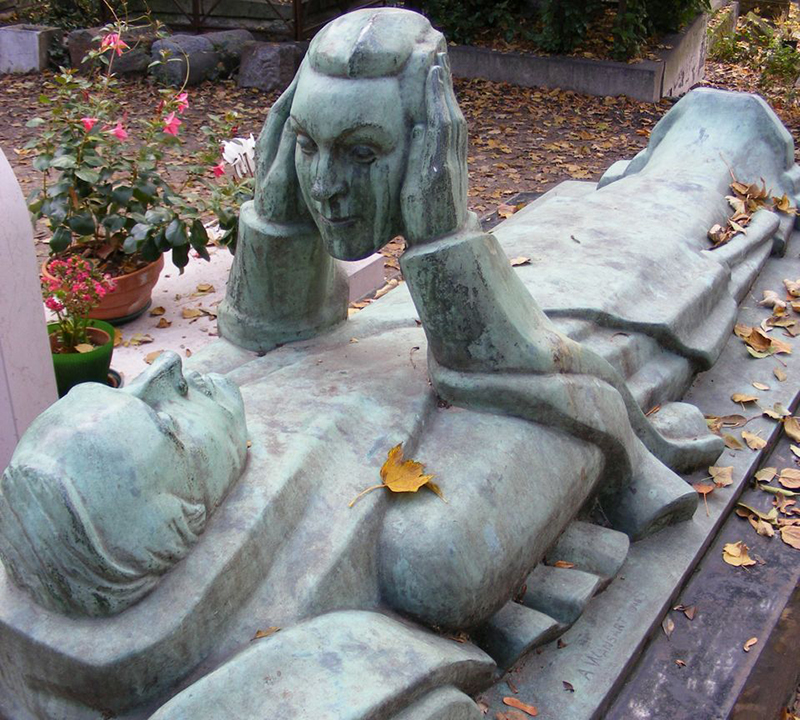 A headstone is a statue of a laying man holding a severed head