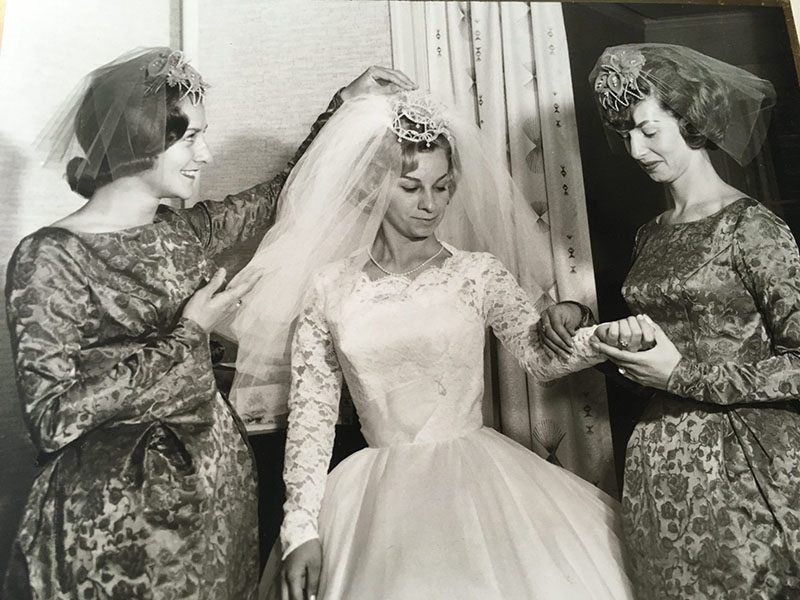 Two bridesmaids help Marguerite prepare for the ceremony