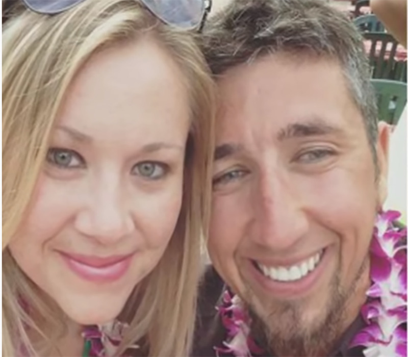 Mr. and Mrs. Kapsidis take a selfie smiling and wearing Hawaiian leis