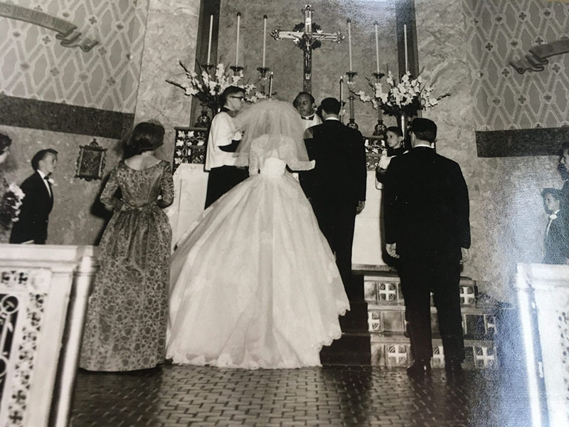 Marguerite and Joseph are photographed from behind while standing at the alter