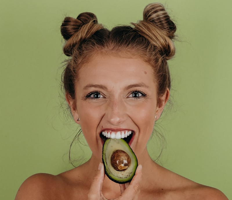 Woman happily eats an avocado in Lincoln, Nebraska