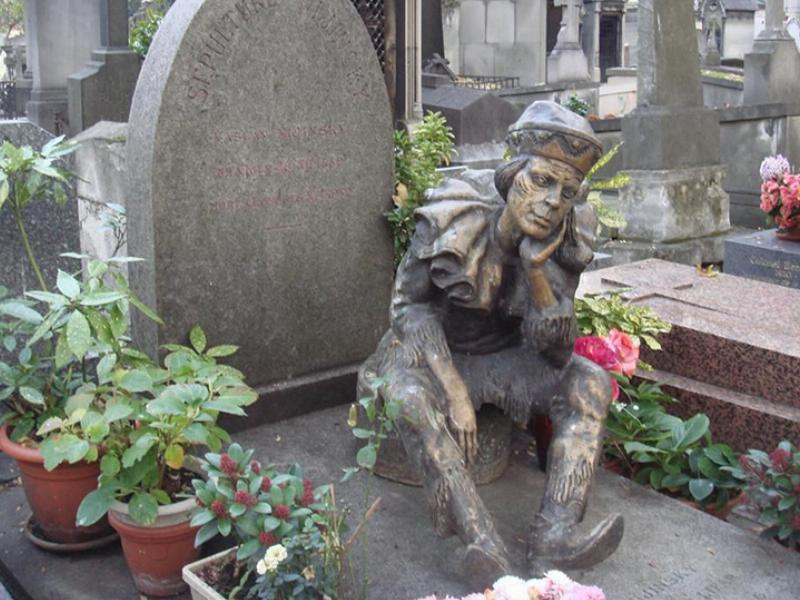 The statue of a small man sits on a grave