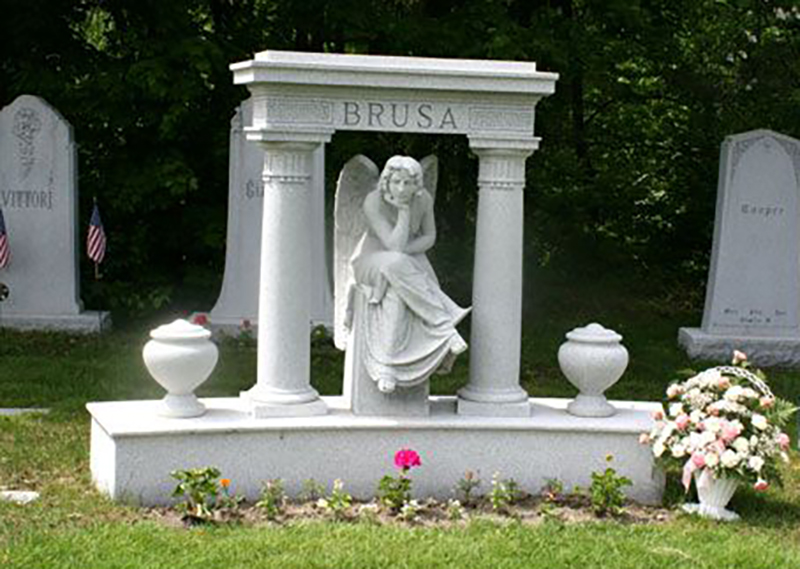An headstone shows an angel statue leaning her chin into her palm