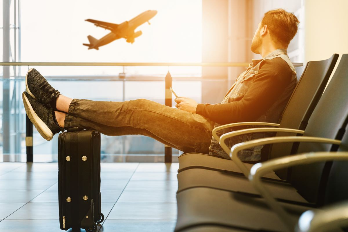 Man waits at a gate and rests his feet on top of his luggage