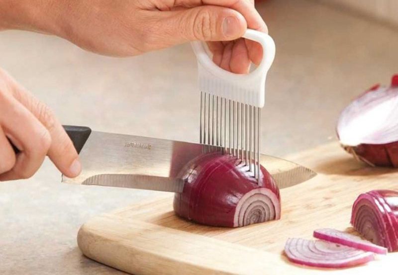 Person uses stainless steel onion holder to chop their onion