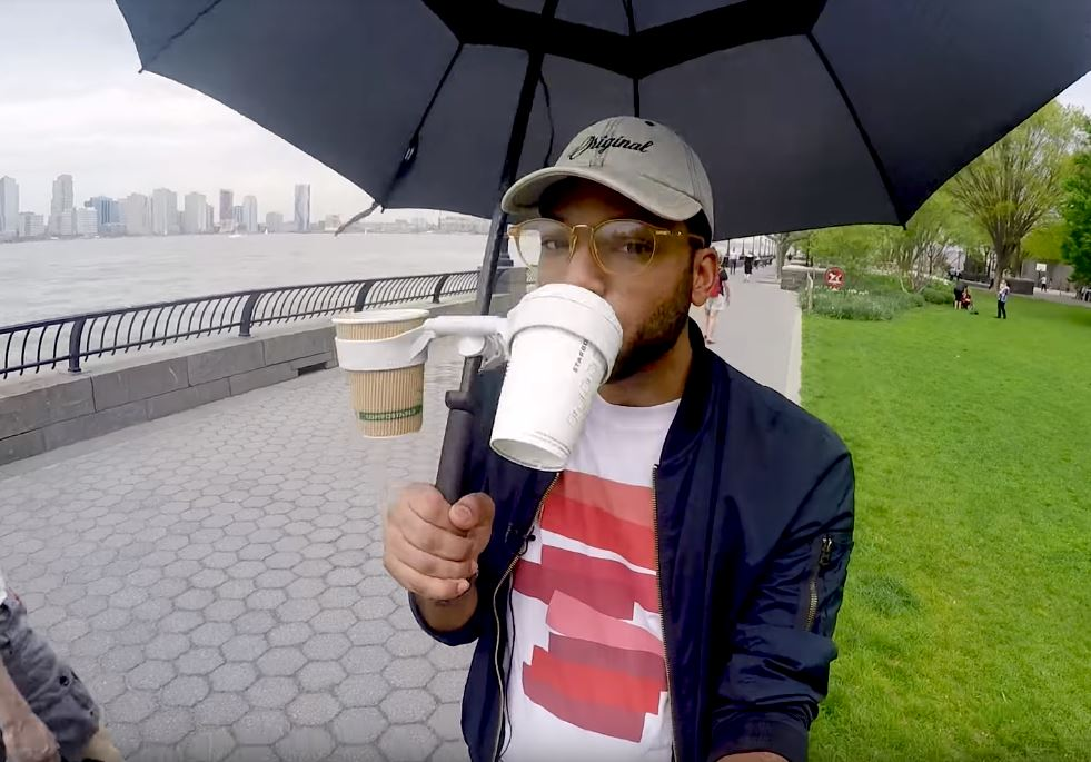 Man drinks from coffee in Morella Umbrella Cup Holder