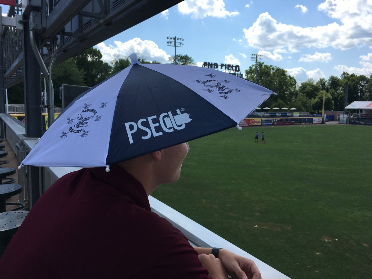 Man wears a Mayfly minor league baseball umbrella hat