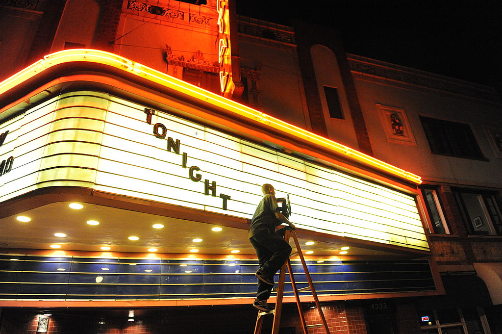 Man putting up theater sign