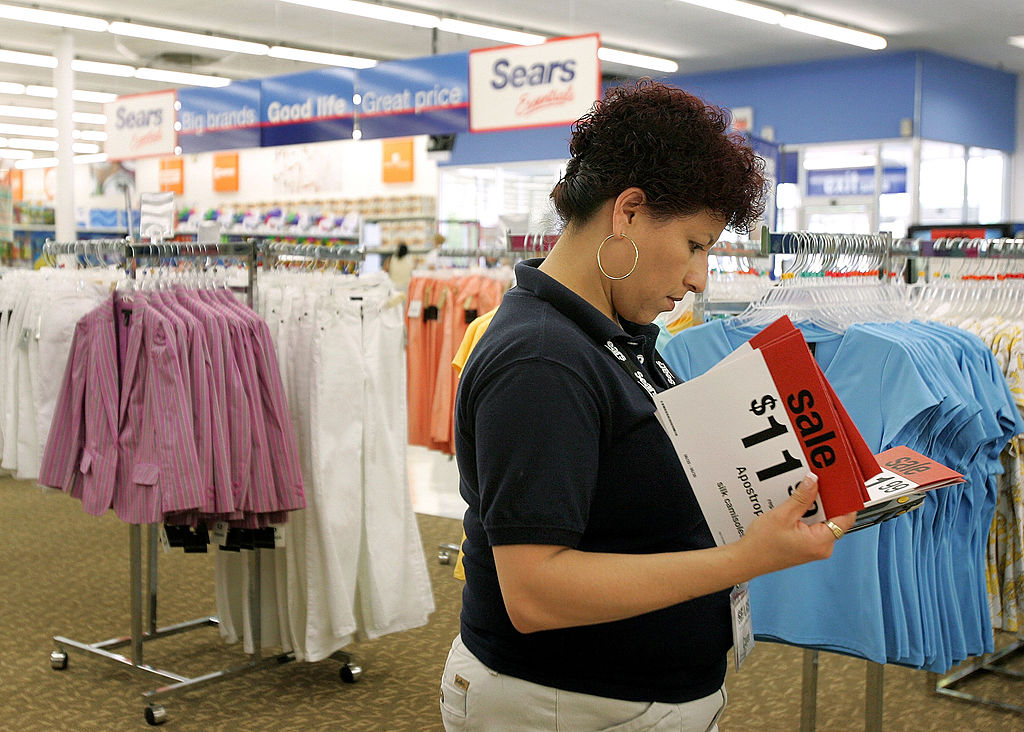 Woman sorting through sales signs