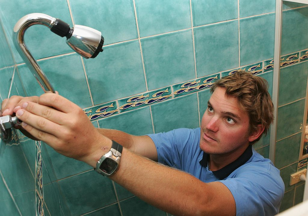 Guy fixing showerhead