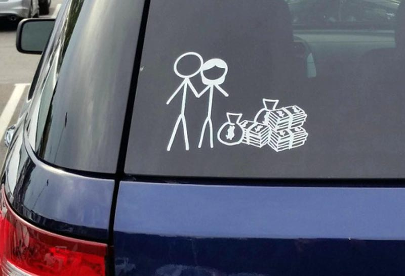 A sticker figure couple is next to a pile of money in a funny bumper sticker.