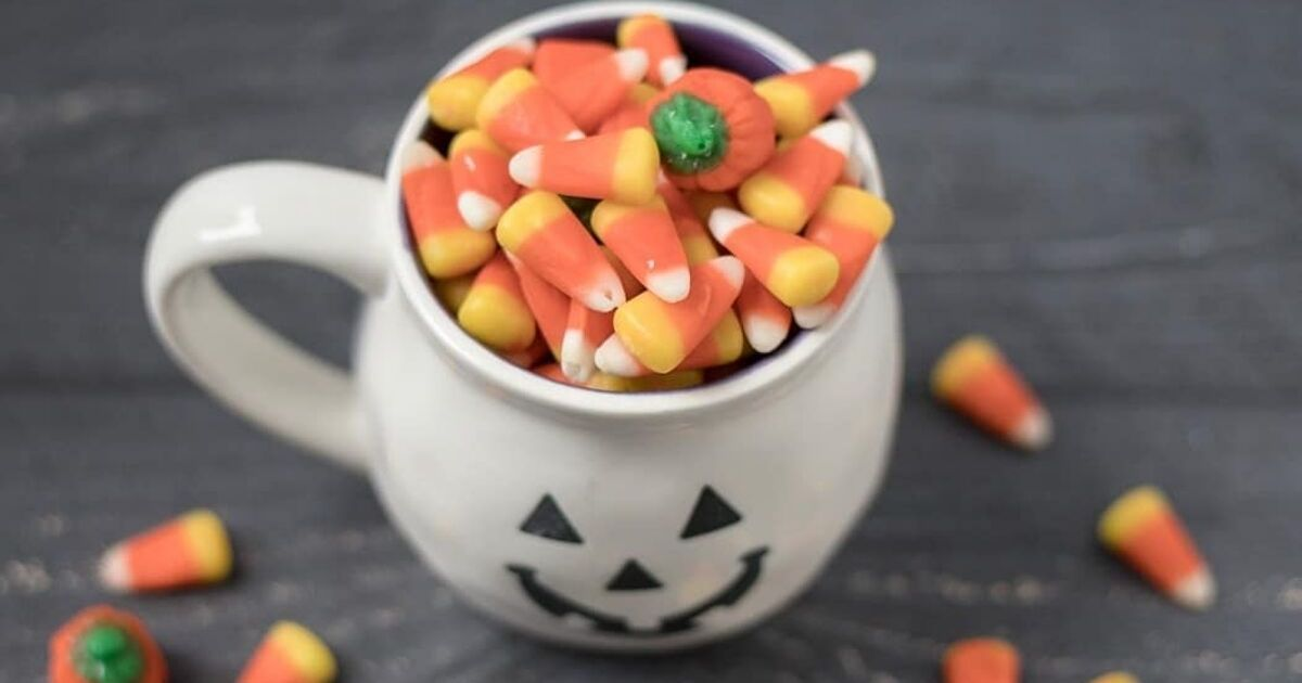 A pumpkin mug overflowing with candy corn.