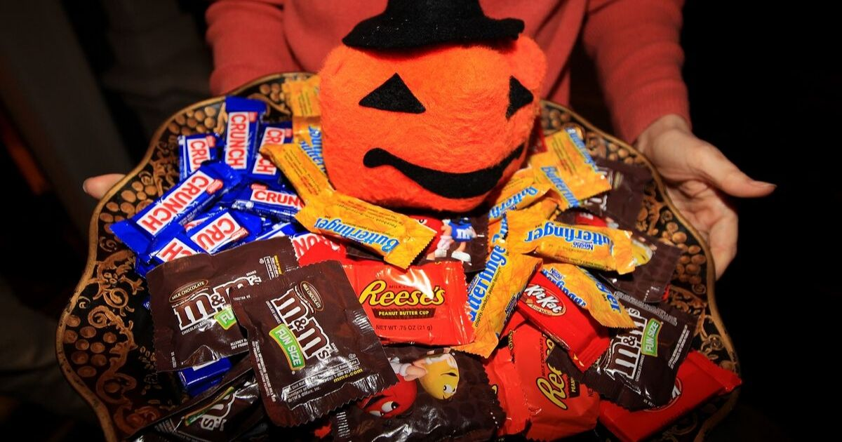 A woman holds a bowl full of Halloween candy