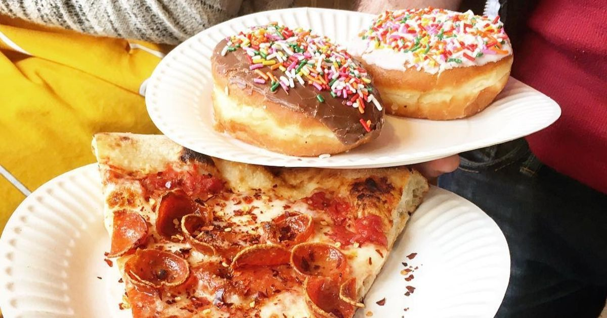 two donuts on a plate above a slice of pepperoni pizza