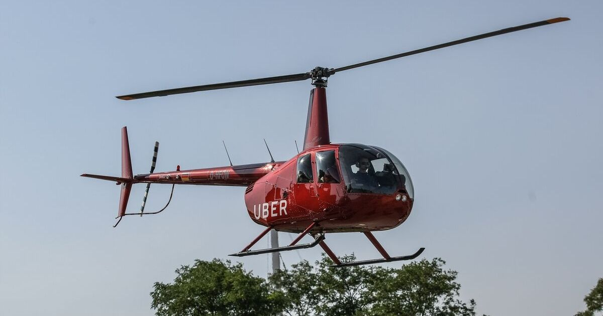 A red UberChopper helicopter flies in the air