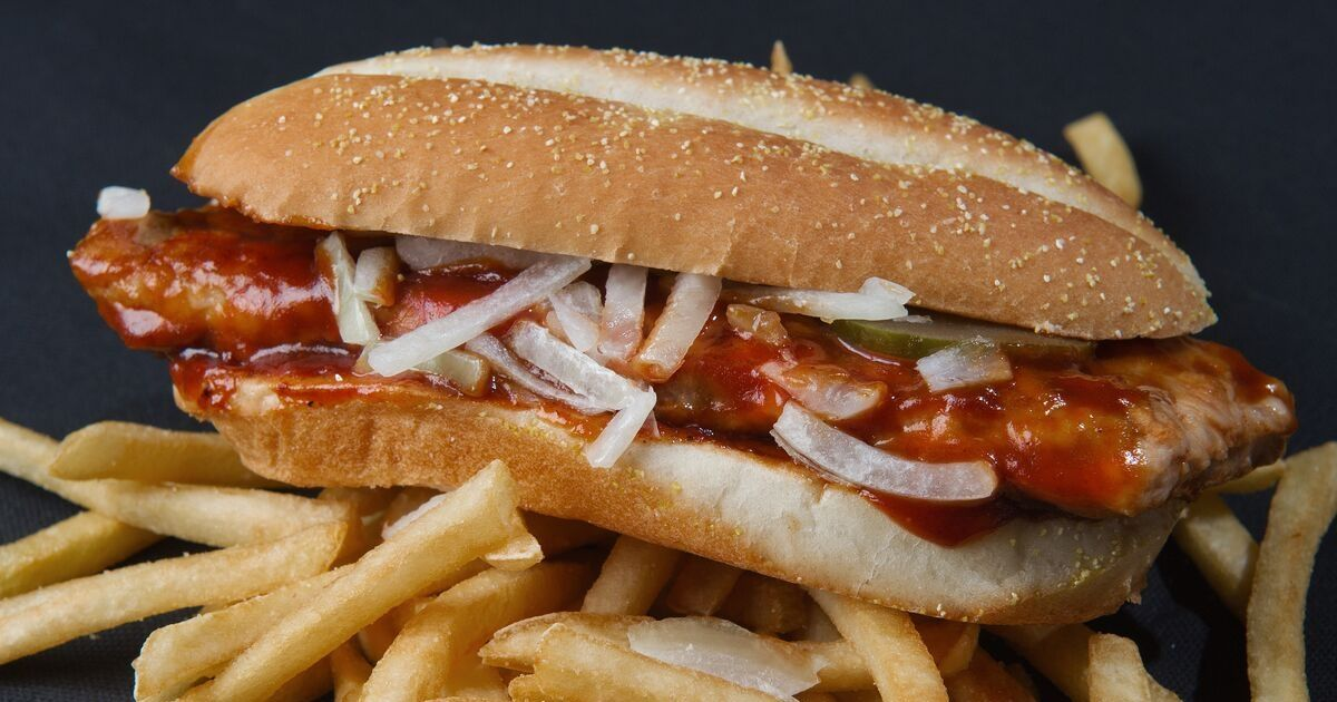 A McRib sandwich perched on to of a pile of McDonald's french fries