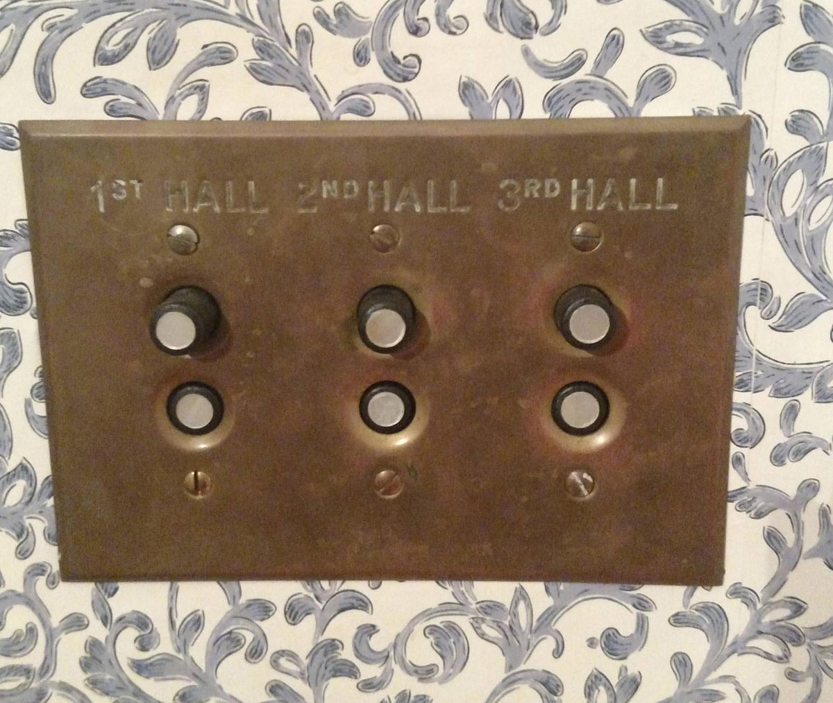 Old-fashioned button light switches hang on a wall.