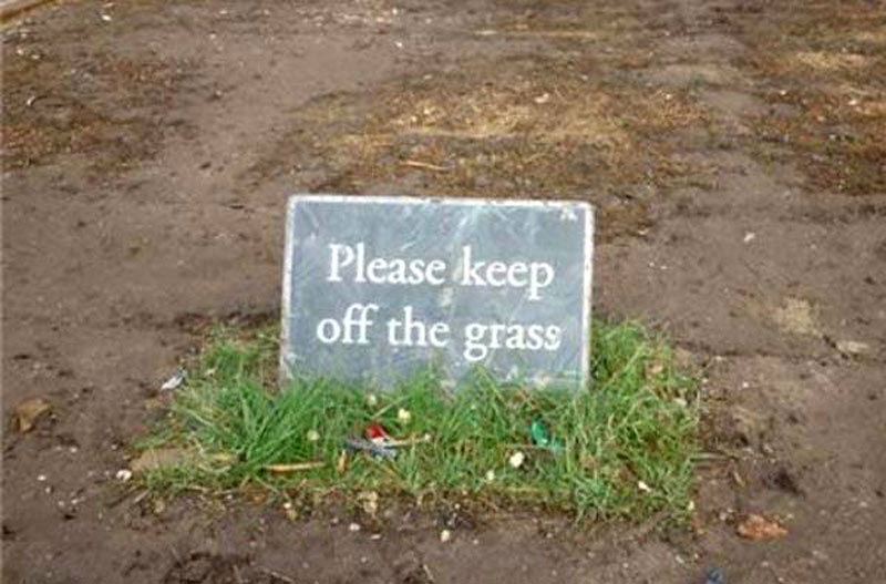 A muddy field offers a tiny patch of grass with a sign that reads