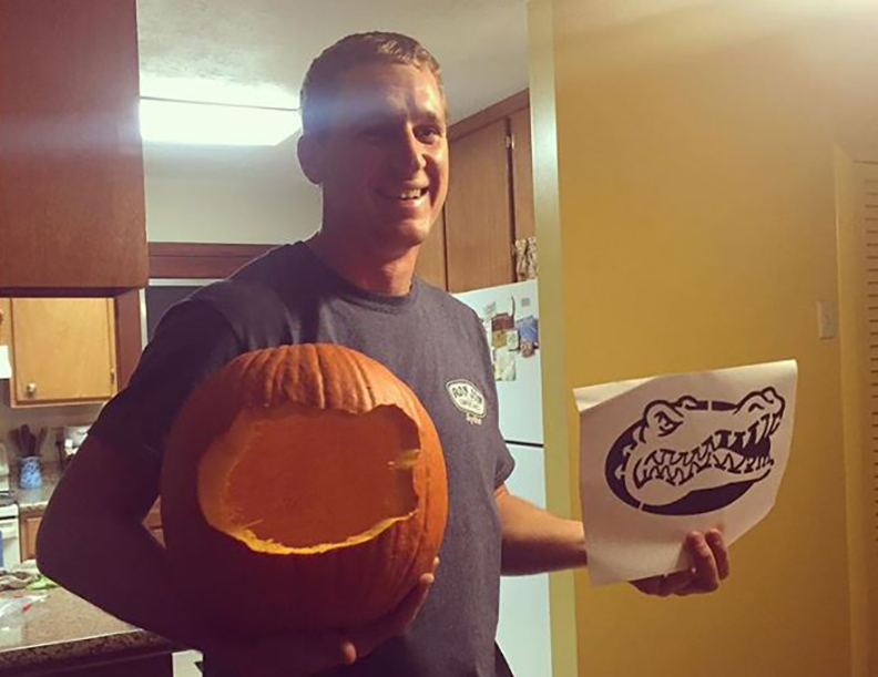 Brother holds up a pumpkin carving fail next to the intended design
