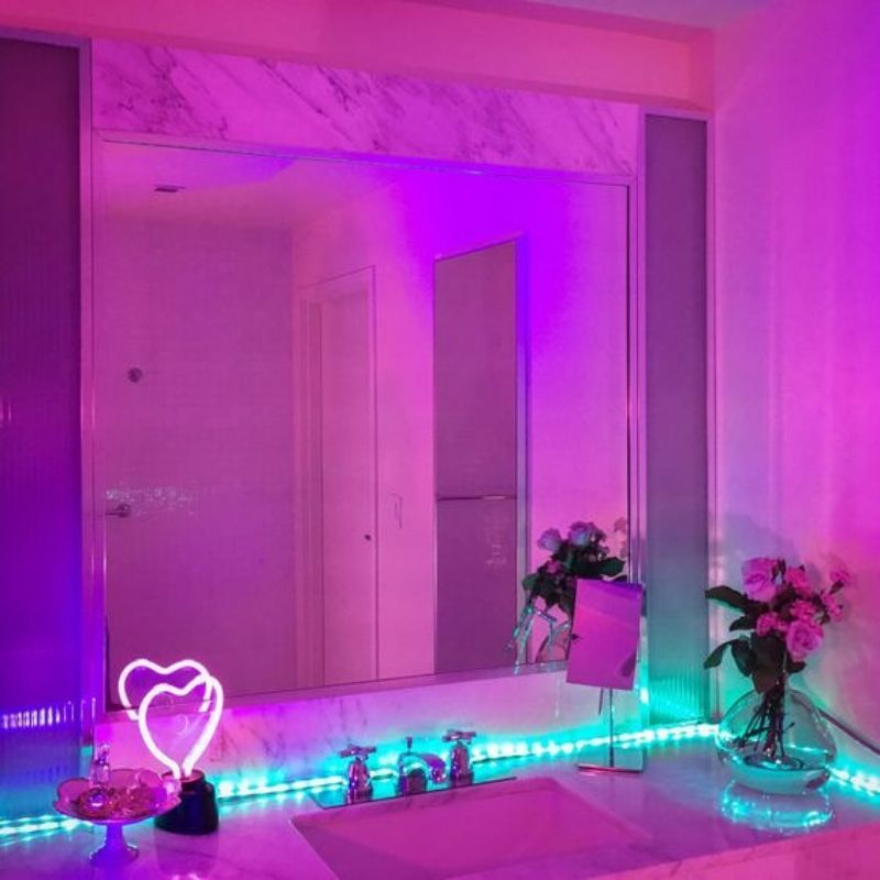 bathroom mirror with neon blue lights around it