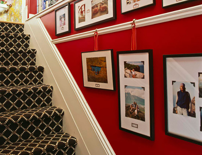 Photos hang from white picture rails against a red wall.