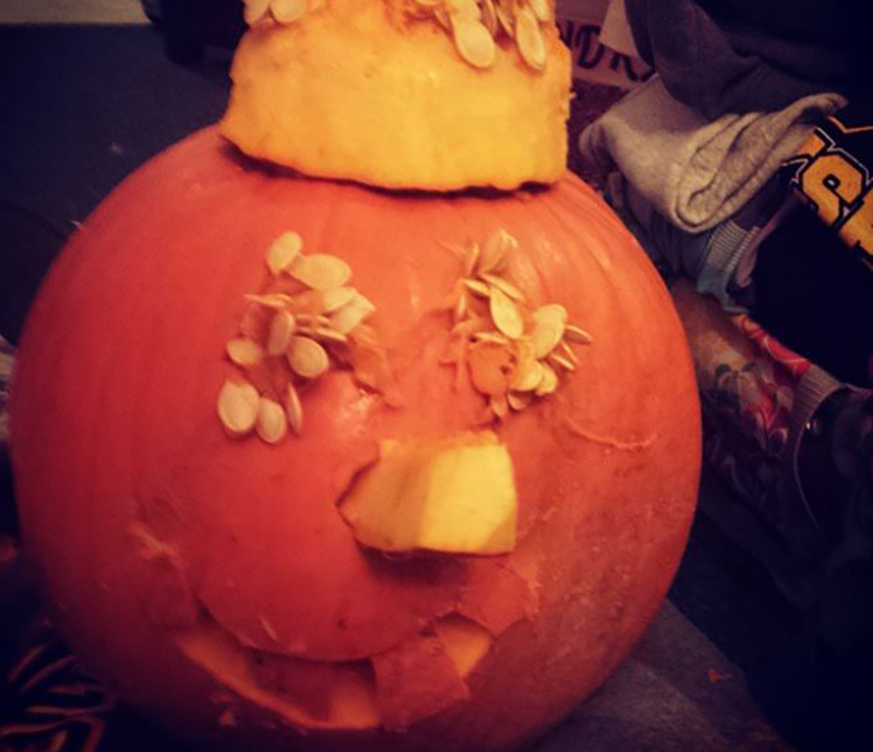 Jack-o'-lantern's eyes and nose stuffed with pumpkin seeds