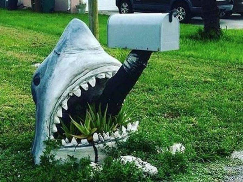 A shark coming out of the grass is attatched to a mailbox via a fake leg.