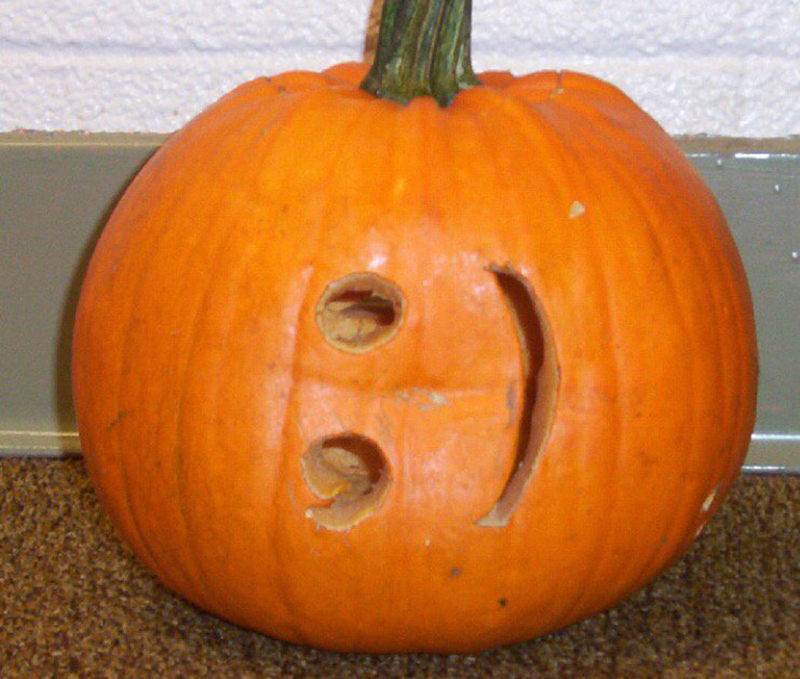 Pumpkin with a carved sideways smiley face
