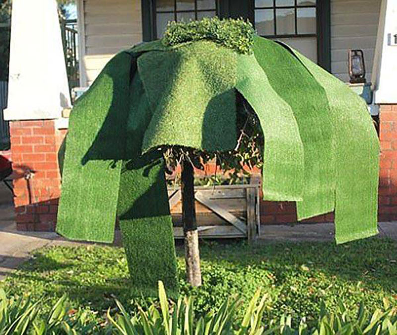 Large strips of fake grass lay over the canopy of a tree.