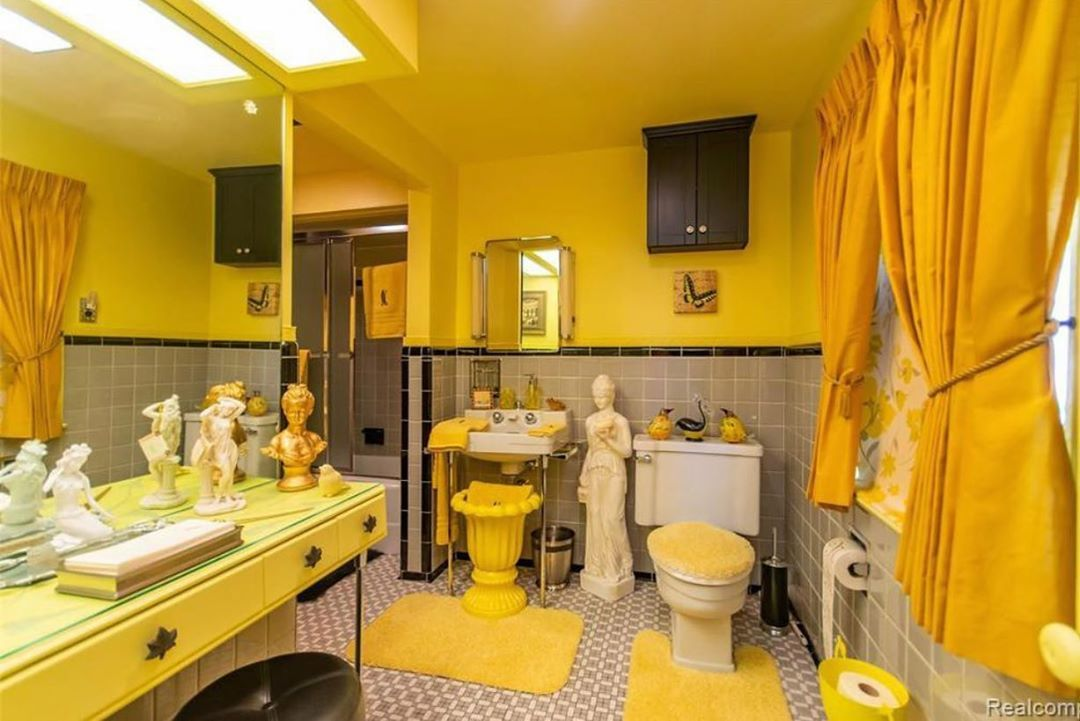 greek statue in all-yellow bathroom