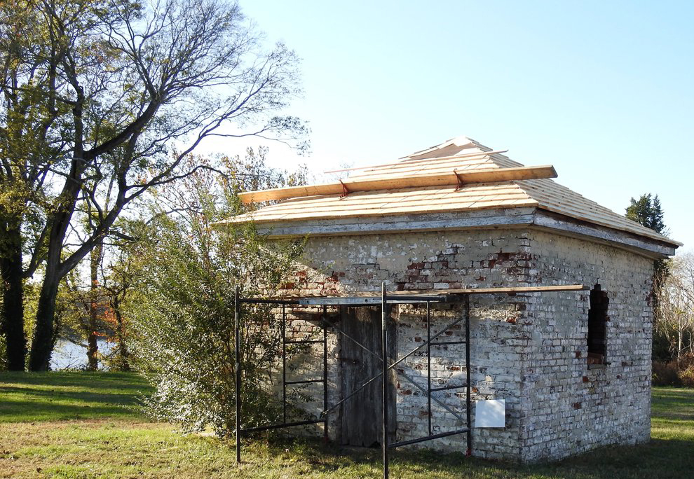 A historical stone summer kitchen stands with iron bars.