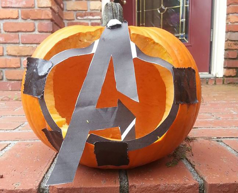 Carved pumpkin remedied with tape shaped like the Avengers logo