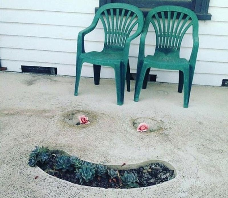 A smiley face is formed in the ground with succelents as a mouth and roses for eyes.