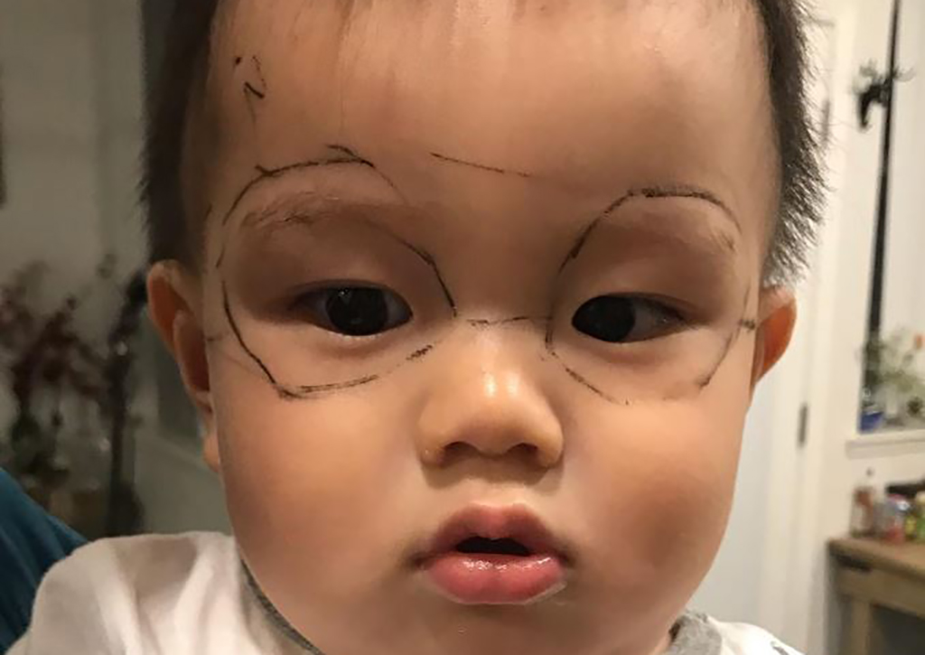 Baby with drawn on glasses