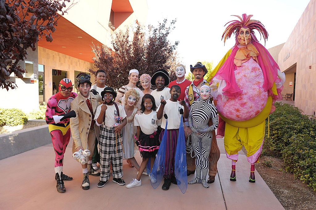 Cast members of Cirque du Monde pose for photos with students