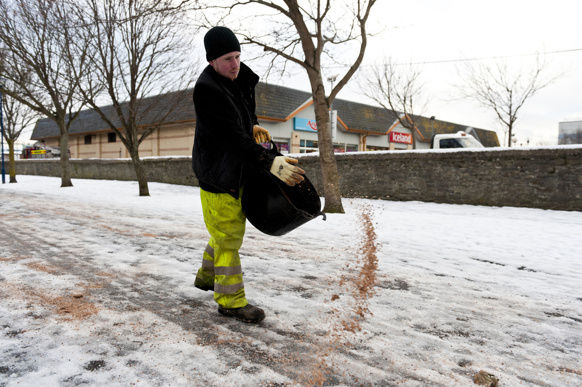 Local authority council workers spread grit and salt by hand on icy footpath to a school.