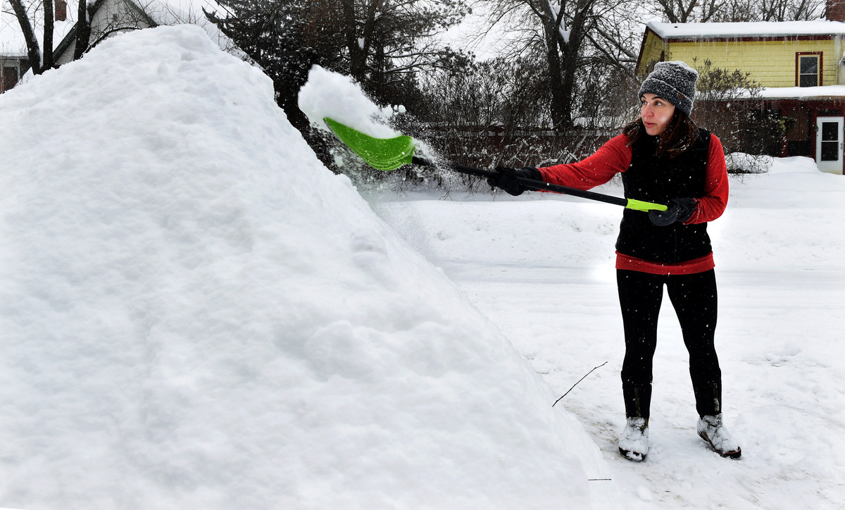 A woman shovels snow into a pile.