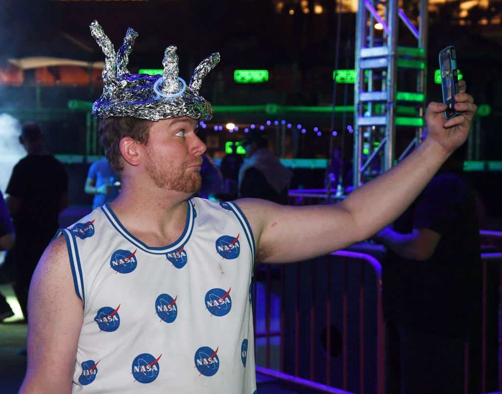 Blaine Adams of California takes video of himself wearing a hat made out of tin foil