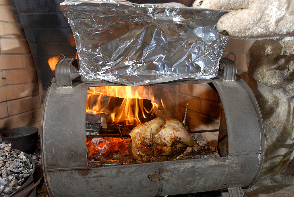 Suzanne Goldenson cooks a meal on an open hearth fireplace