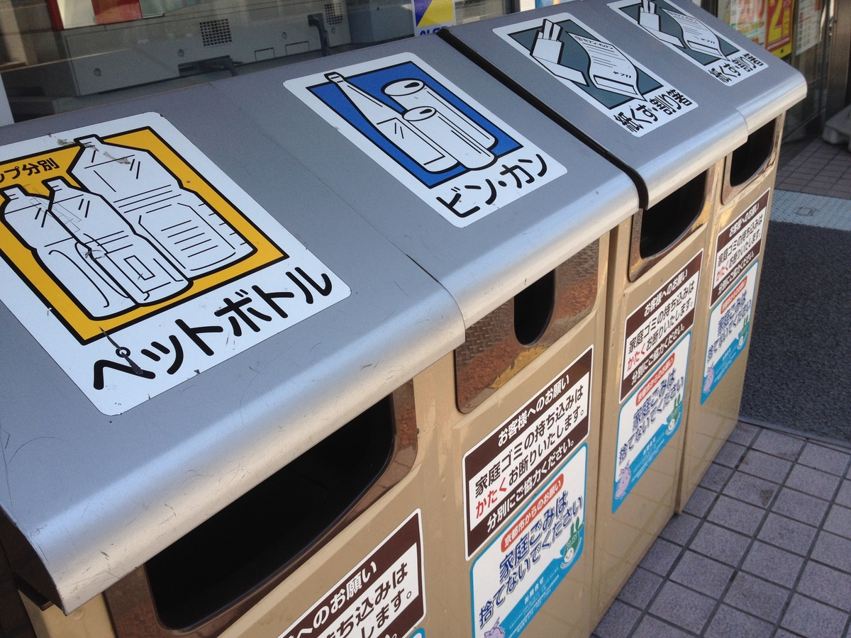 Trash cans and recycling bins line a street in Japan.
