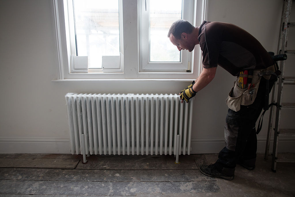 A builder fits a radiator to the wall