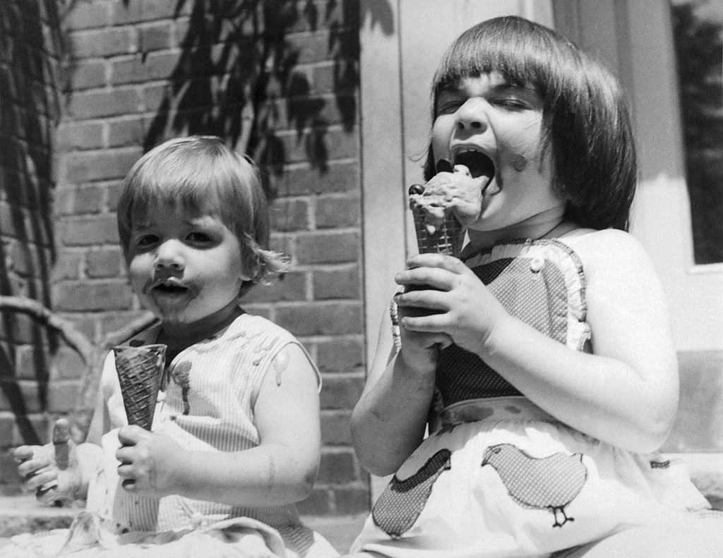 Demitra, 2, (left) and Darcy, 4, enjoy the summertime weather while eating and dripping their chocolate ice cream cones. The drips on the clothes and arms may mean clean up chores for Mother but the girls seem to be enjoying themselves too much to care.