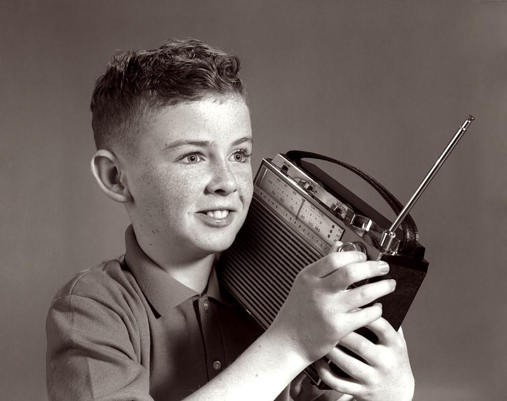 a boy listening to a portable radio